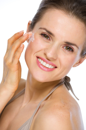Beauty portrait of happy young woman applying creme